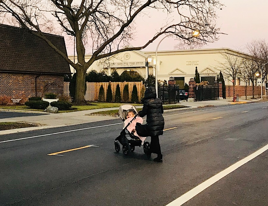 A woman pushes a stroller to Congregation Shaarei Tzedek Mishkan Yair in West Rogers Park at Sundown on a Friday evening. Without the eruv, using the pram would violate Sabbath rules.