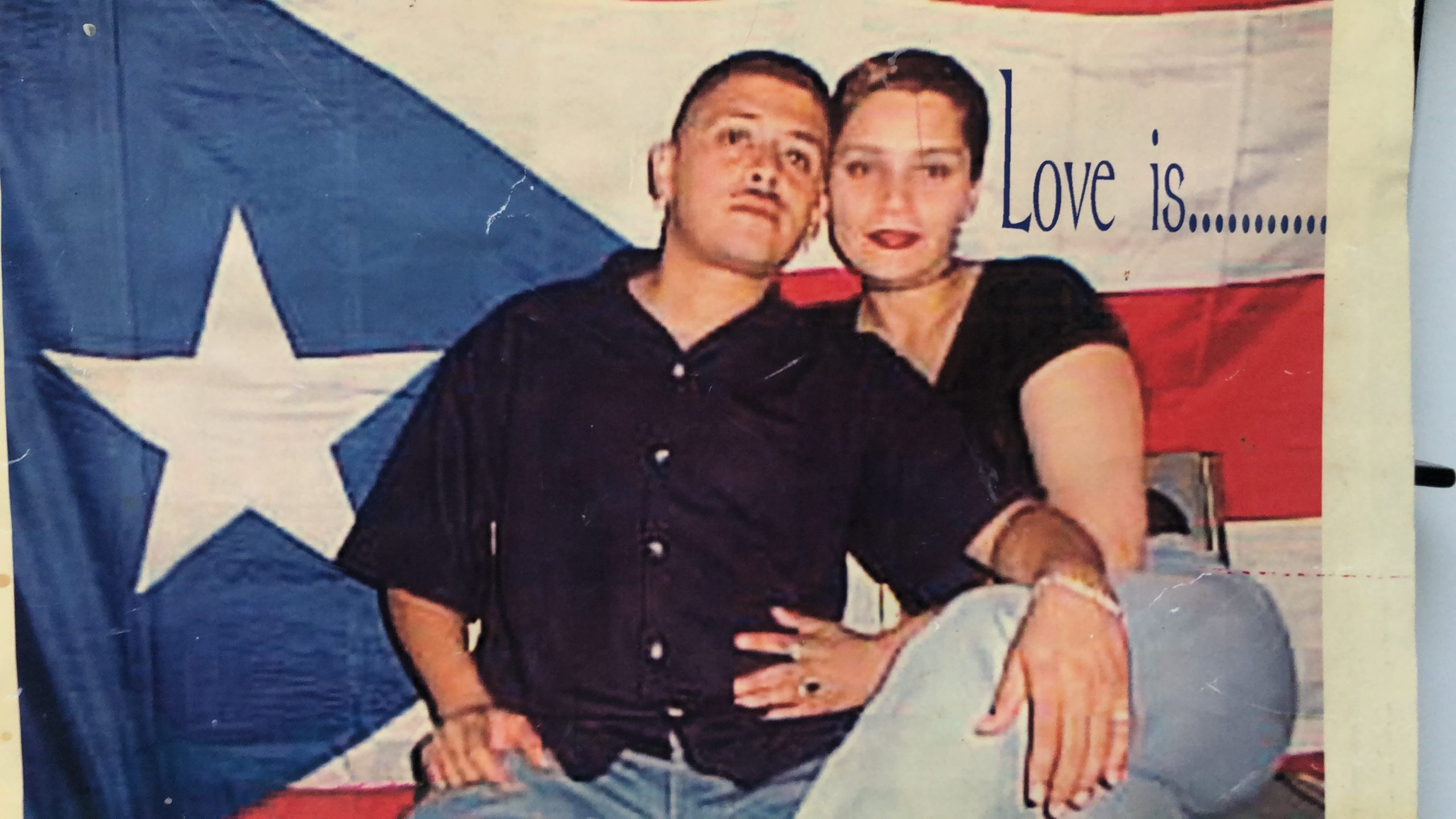 Justin Agrelo's parents, sitting happily in front of a bright Puerto Rican flag.