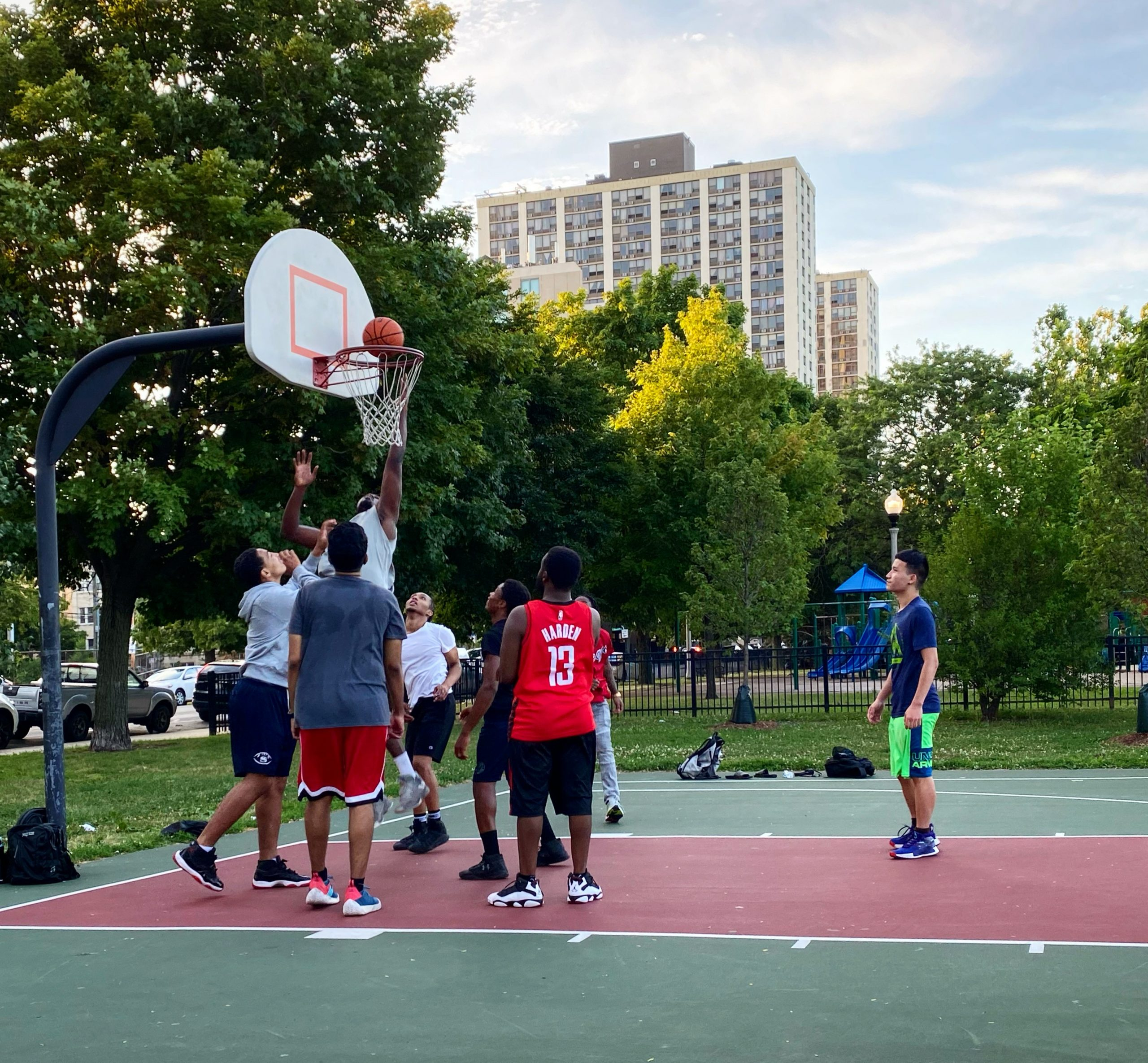 Ken Mason (red jersey) playing at the Clarendon Park basketball court in Uptown for the first time in July since the start of the pandemic. Mason had observed gentrified neighborhoods were less policed and impacted during the shutdown compared to the south and west sides of the city.