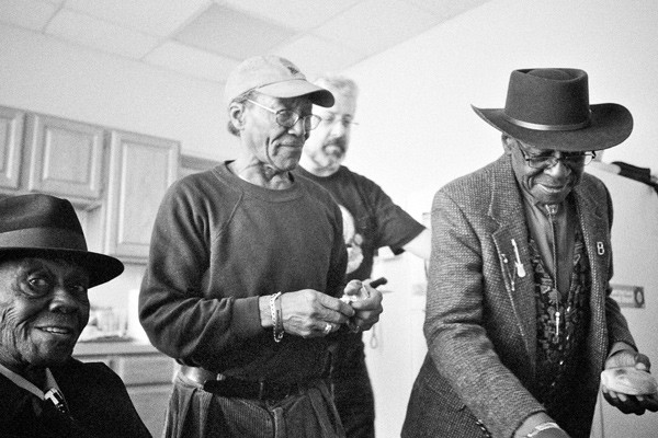 """Pinetop Perkins, Willie """"Big Eyes"""" Smith, and Bob Stroger take a bagel break in the studio's kitchen. The author is in the background.  """"Pine was like a brother and a father to me. He is the reason why I play the blues,"""" Stroger said."""