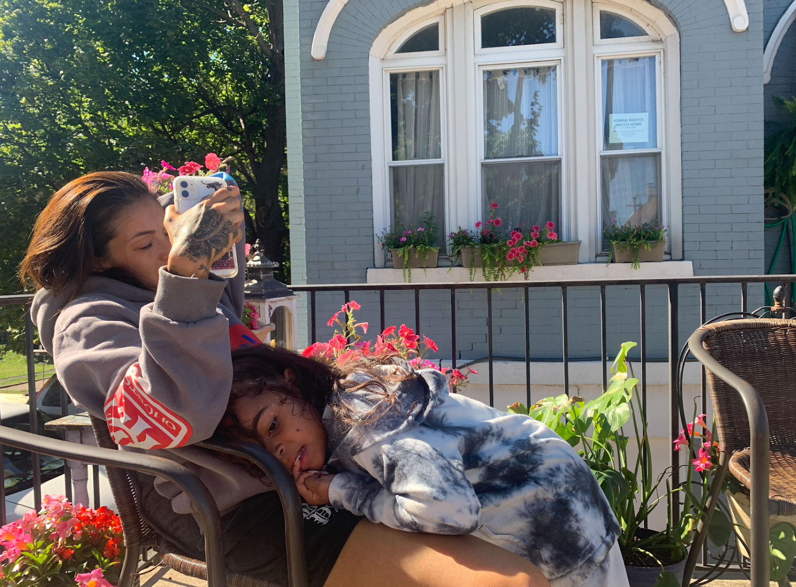Tanya Lozano chats on FaceTime outside of her family home with daughter Apollonia Jackson in her lap.