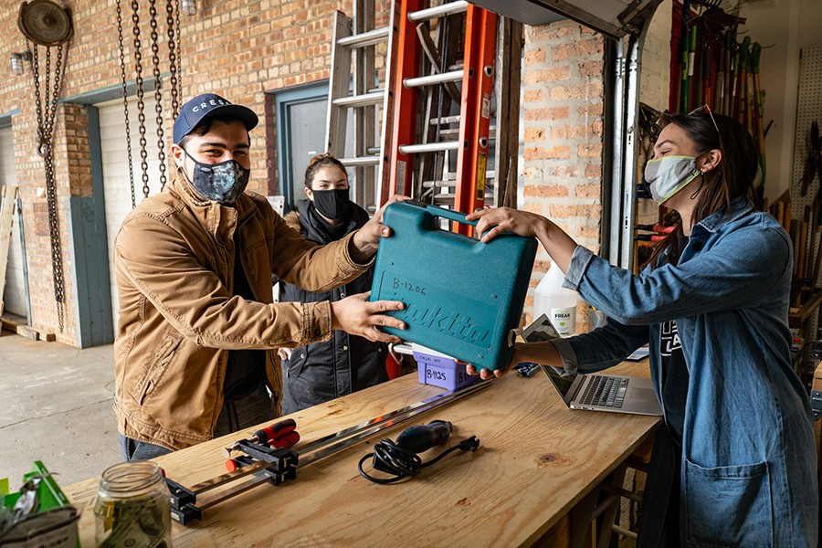 Tessa Vierk hands off power tools to Chicago Tool Library customer.