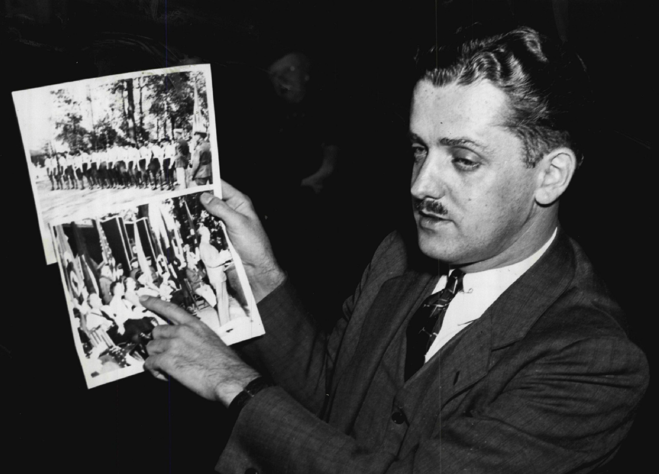 <i>Chicago Daily Times</i> reporter and former FBI agent James C. Metcalfe showing congressional investigators a photo of Kuhn meeting with German consular officials in Chicago.