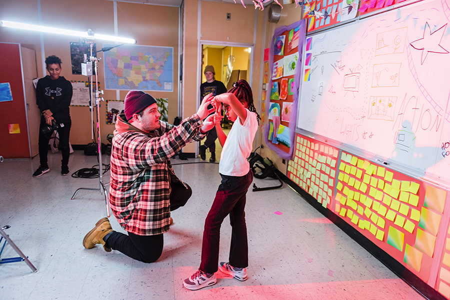 Connor Wiles shows nine-year-old Danielle Reed, who plays the director of the video, how to frame a shot with her hands.