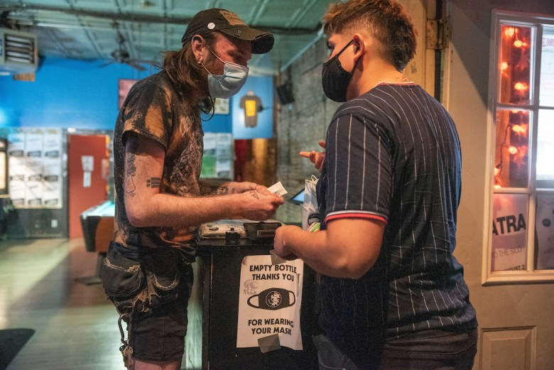 Sean Nyary, 30, checks identification and vaccination cards at the entrance to the Empty Bottle on August 27, 2021.