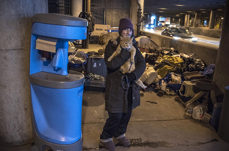 Stacey holds Simba and stands next to a portable wash station; March 15, 2020