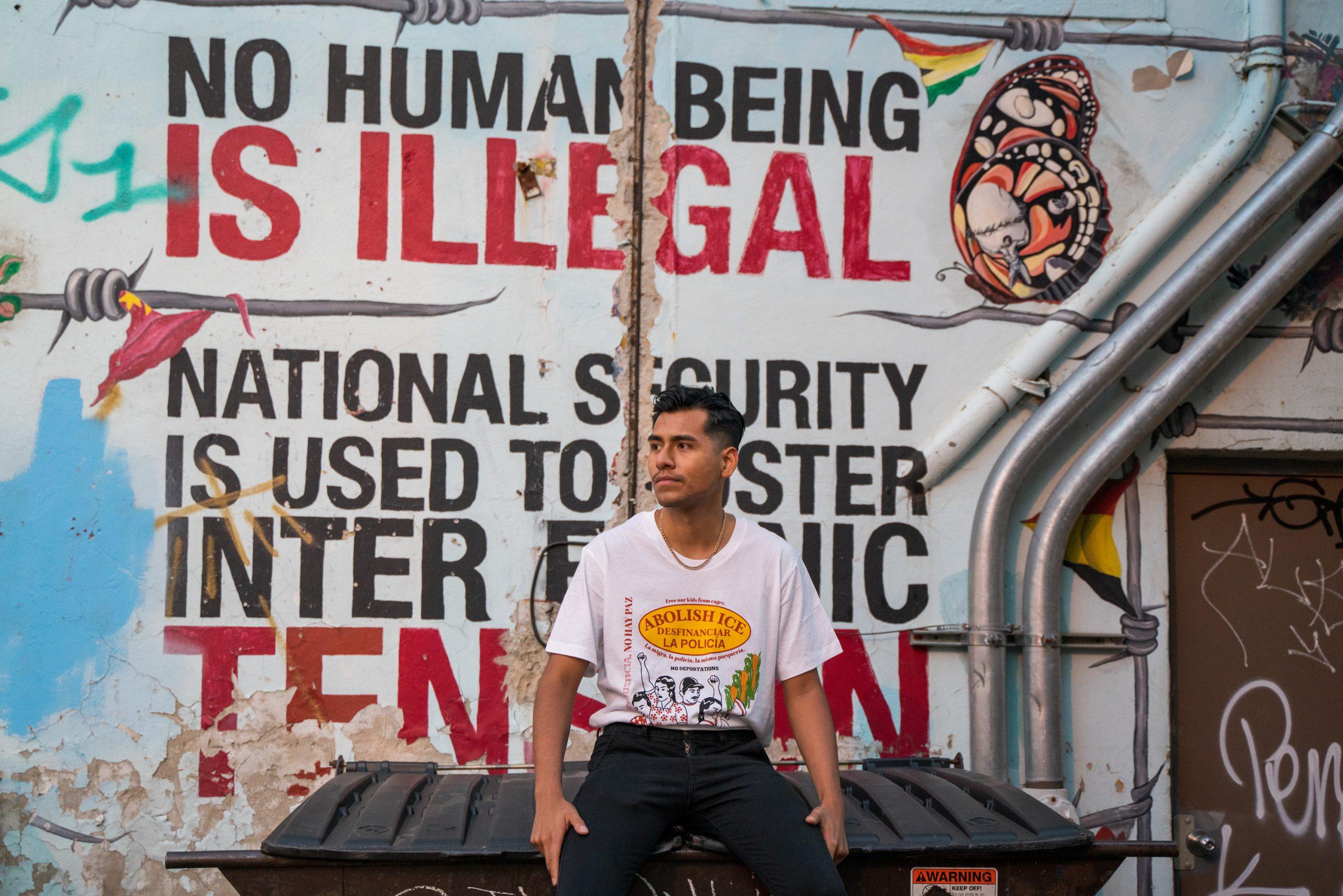 Fernando Delgado wears his T-shirt in front of a mural celebrating immigrants in Pilsen.