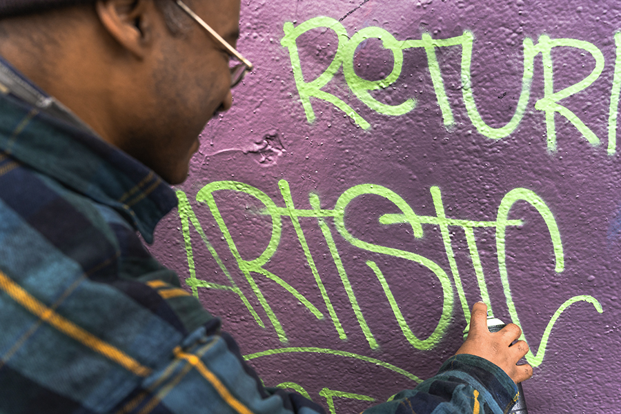 """Roberts leaves his """"Artistic"""" signature on the mural at the Logan Square permission wall."""