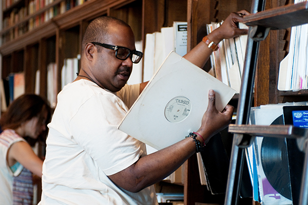 """Frederick Dunson, executive director of the Frankie Knuckles Foundation, checks out a 1979 promotional copy of the Ish single """"Don't Stop"""" from his old friend's collection."""