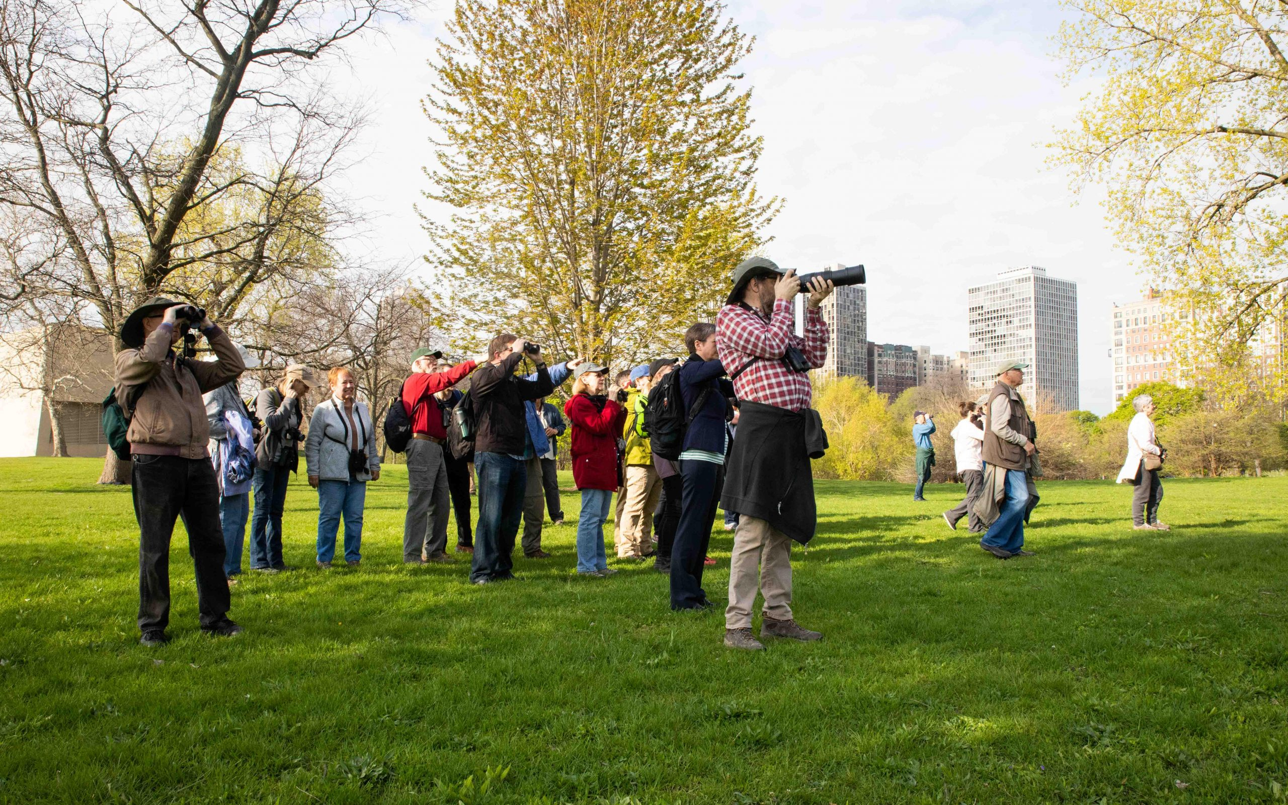 Participants stop to observe birds as they make their way around the water during the Chicago Ornithological Society's North Pond Bird Walk in May 2019.