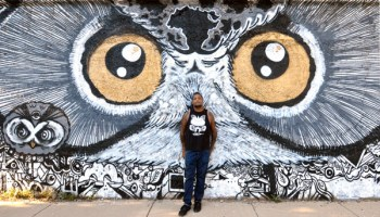 Brooks Golden, in August 2012, with the owl mural he painted along the 16th Street viaduct in Pilsen