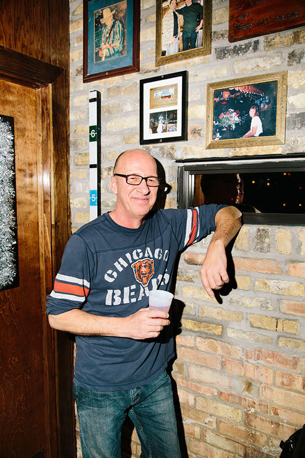 Bob Hirtzig, brother of former Carol's owner Carol Harris, poses with a photo of Harris at the bar (above his left elbow).