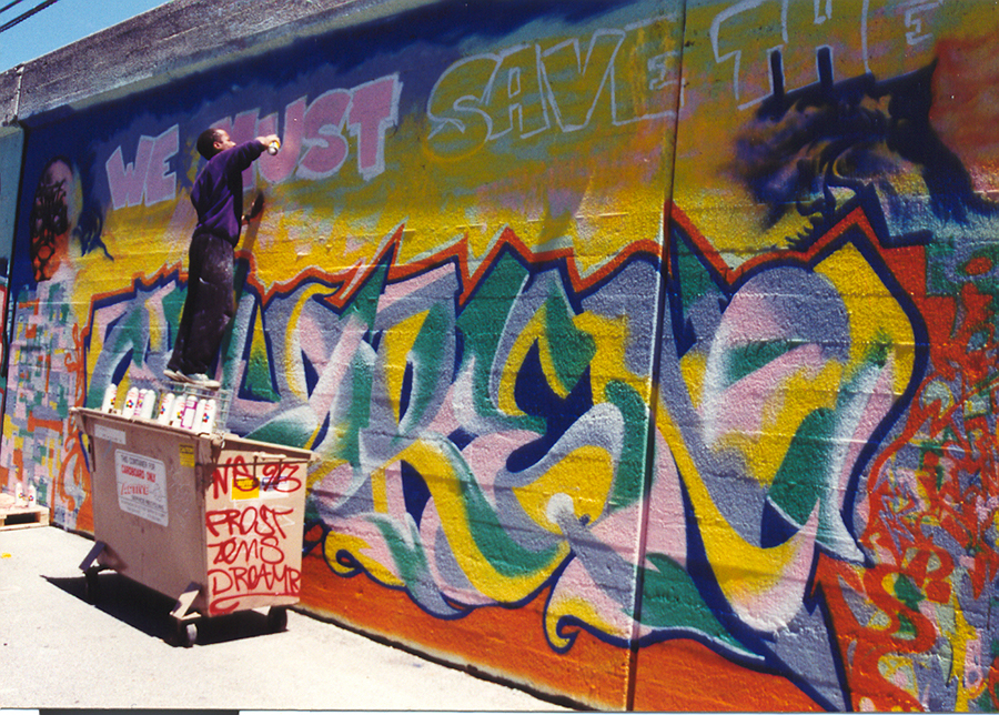"""Roberts paints """"We Must Save the Children"""" on a retaining wall near the Berwyn Red Line stop in 1995 as part of a citywide CTA project."""