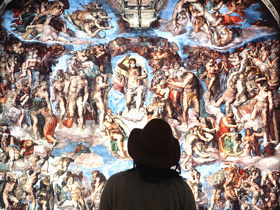 A viewer takes in Michelangelo's The Last Judgment.