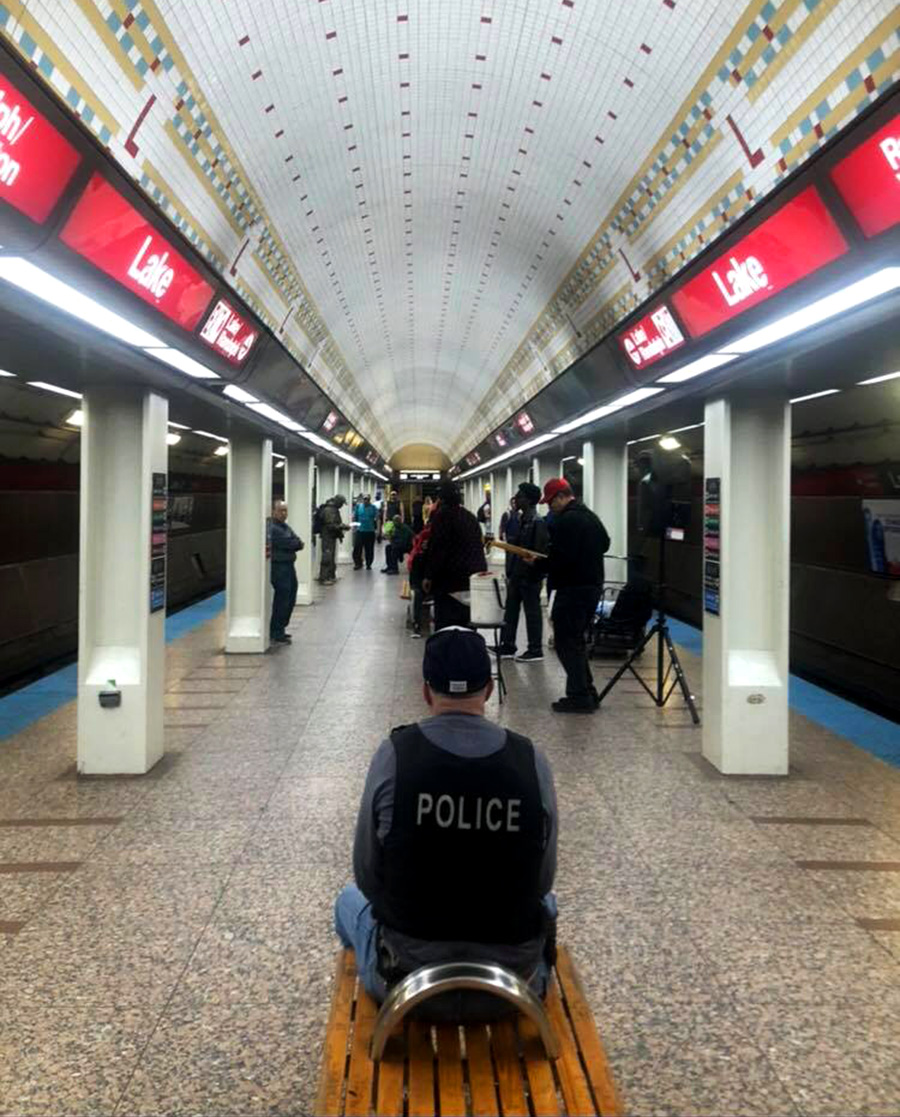 Johnston recently captured this photo of a police officer listening to a band perform at the Lake Red Line station—an unauthorized performance location.