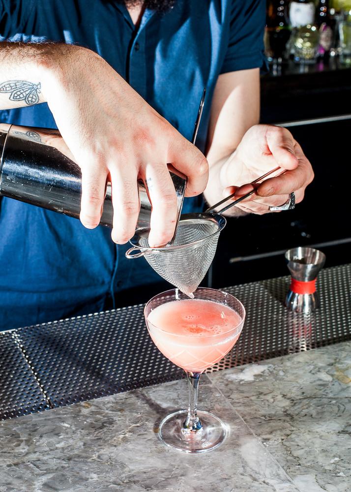 Bartender making the La Coqueta cocktail