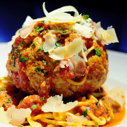 A softball-size meatball and pasta