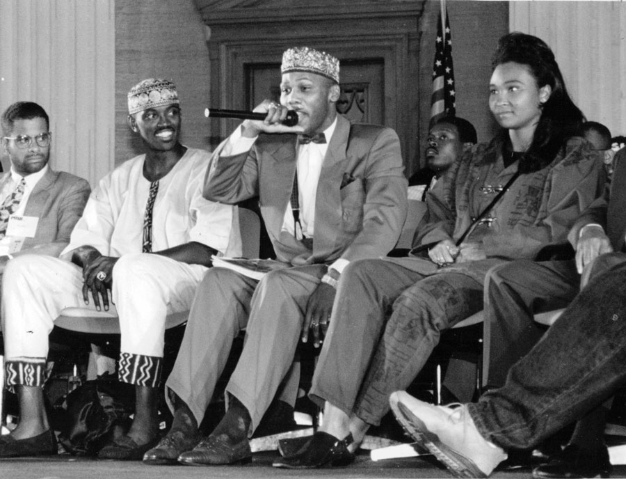 """In September 1992, Craig Hodges (seated second from left) joined rappers Prince Akeem (pictured holding the microphone, second from right) and May May on Youth Empowerment Day at Operation PUSH headquarters. Hodges is not a Muslim but says that he """"studies all religions."""""""