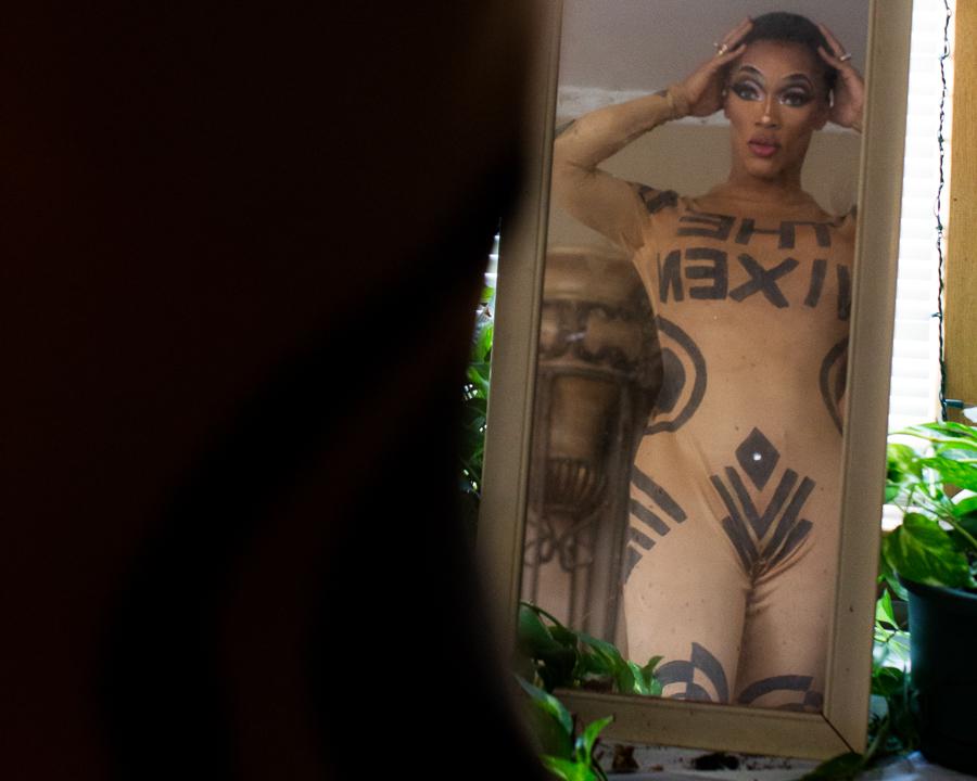 The Vixen straightens her wig cap. Her nude painted costume is handmade.