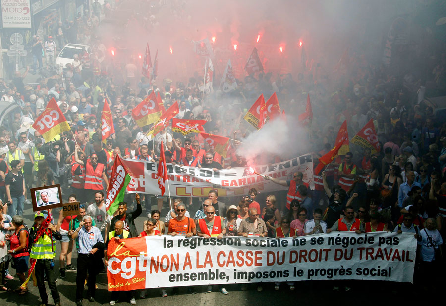 """French protesters hold a banner reading """"You do not negotiate social setbacks, let's impose social progress together. No to scrapping labor law"""" during Tuesday's march."""