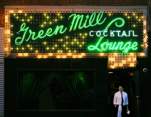 Bartender Jason Cole in front of the iconic Green Mill neon sign