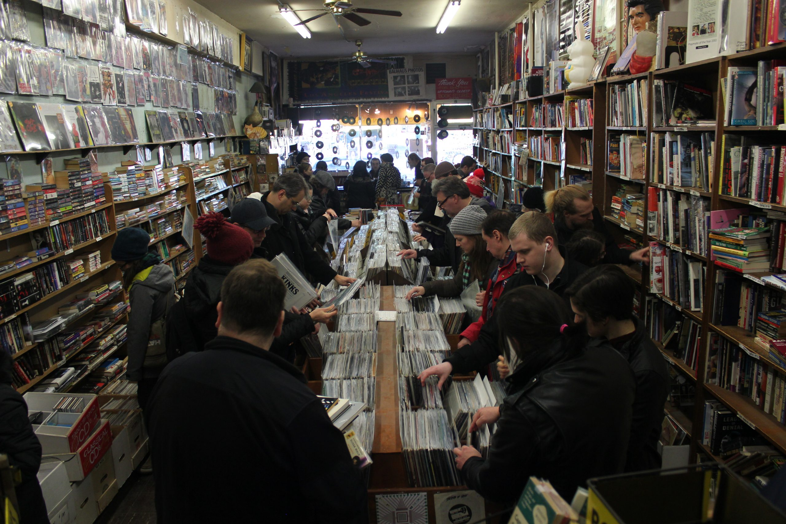 A seemingly endless stream of customers browse the shop's stacks of vinyl, books, CDs, old magazines, band posters, and random junk.