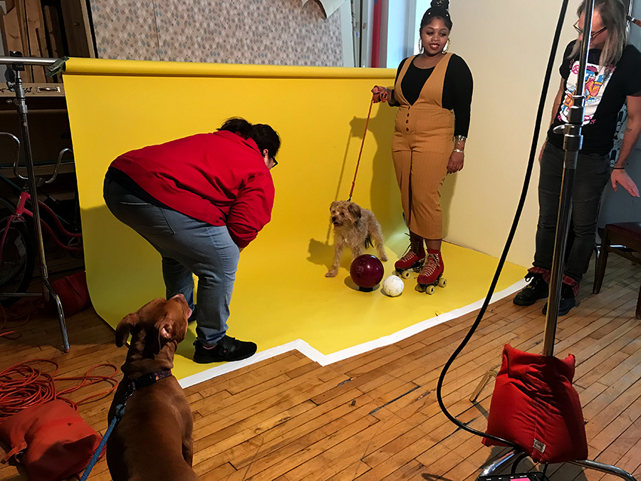 Sports & Rec model Patti needs the encouragement of her dog bestie Ray to prep for the shoot. Janaya holds Ray to set up the shot, while photo assistant Brian Gladkowski is on standby.