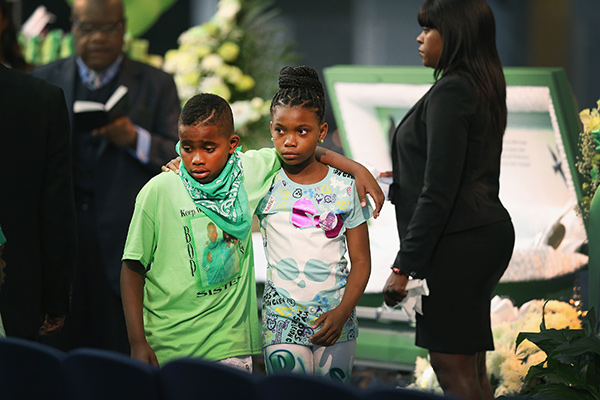 Eleven-year-old Jeremiah Adams (left) walks away from the casket that holds his twin sister, Shamiya.