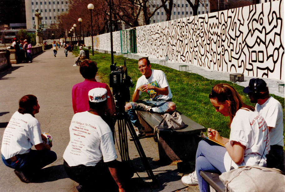 Haring is interviewed in front of the mural in progress.