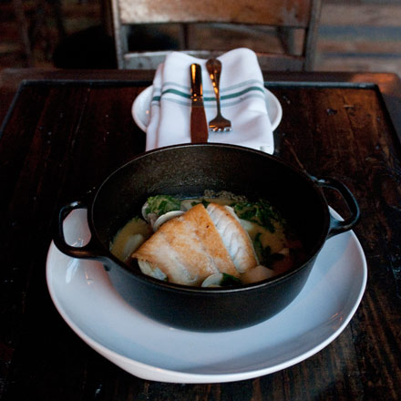 Sea bass en cazuela, bathed in a thin, salty coconut broth spiked weakly with curry