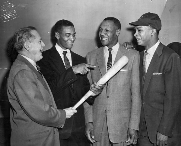In 1955, the Cubs made former Negro League manager Buck O'Neil their first black scout. Shown at the announcement, from left: personnel director Wid Matthews; shortstop Ernie Banks; O'Neil; second baseman Gene Baker.