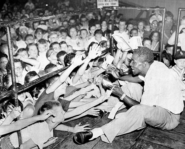 Minnie Minoso, who in 1951 became the first black White Sox player, signs autographs at the Chicago Free Fair in the Back of the Yards neighborhood in 1957.