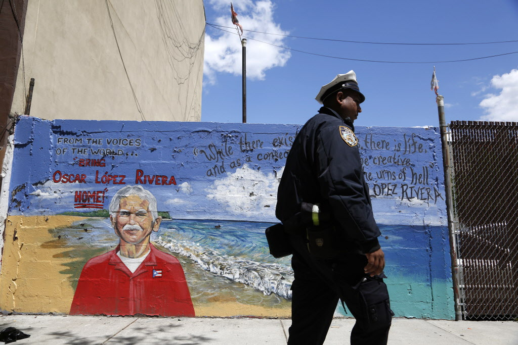 A police officer walks past a mural of Oscar López Rivera in New York.