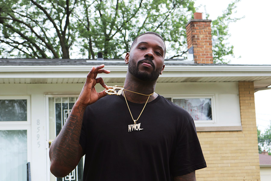 """Phor in front of what used to be his grandma's house in Marynook. His """"87"""" chain represents nearby 87th Street as well as his birth year, and """"NMOL"""" stands for """"No more ordinary lifestyle."""""""