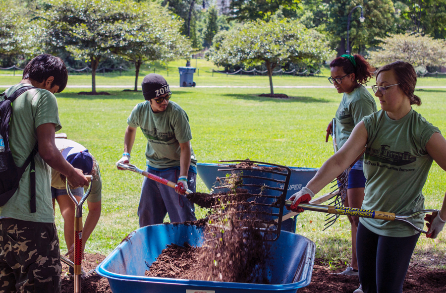 Volunteers spread mulch at a Douglas Park beautification event in August.