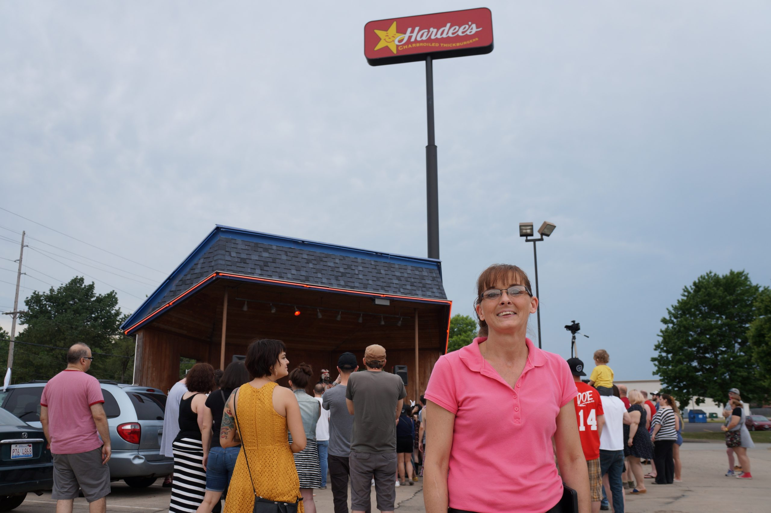 Denice Hubbs, manager of Rock 'n' Roll Hardee's, in front of the Dumb Fest crowd and the restaurant's outdoor stage
