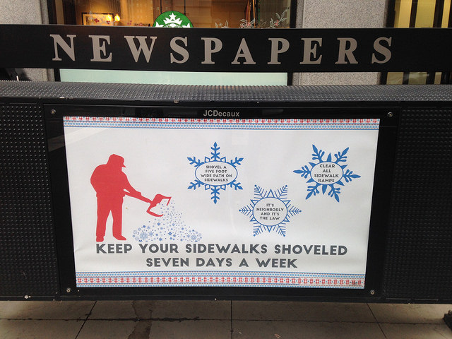 An ad on a Loop newspaper rack reminds residents to shovel.
