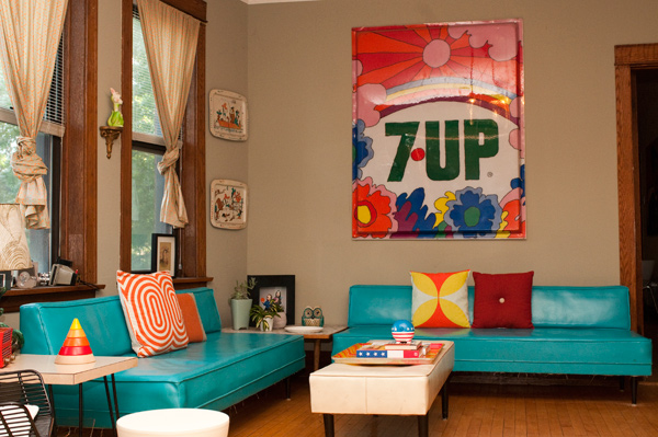 A vintage 7 Up sign from an old convenience store hangs above the couch