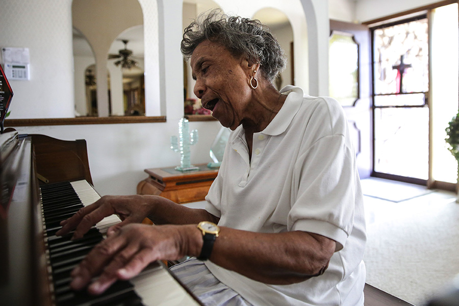 """Mama Lou belts out the hymn """"Pass Me Not, O Gentle Savior"""" on the piano in her home. """"These old fingers don't play so well anymore,"""" she says."""