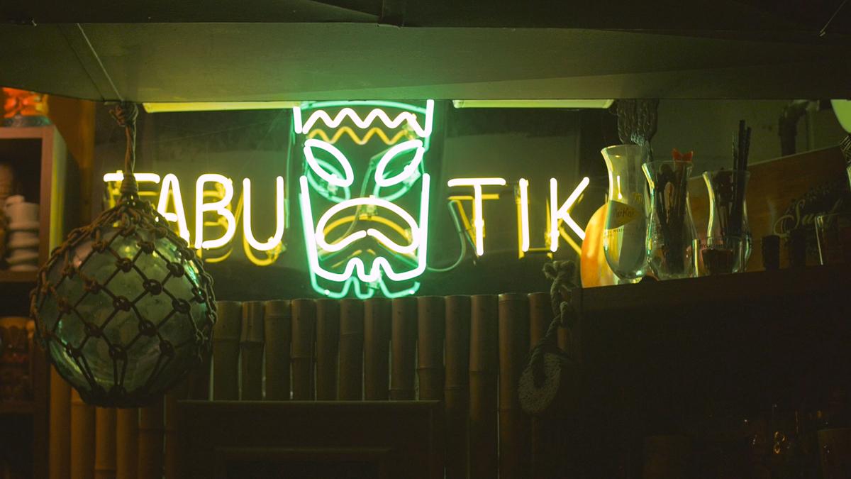 A neon sign marks the Tabu Tiki Room, the Carters' basement bar.
