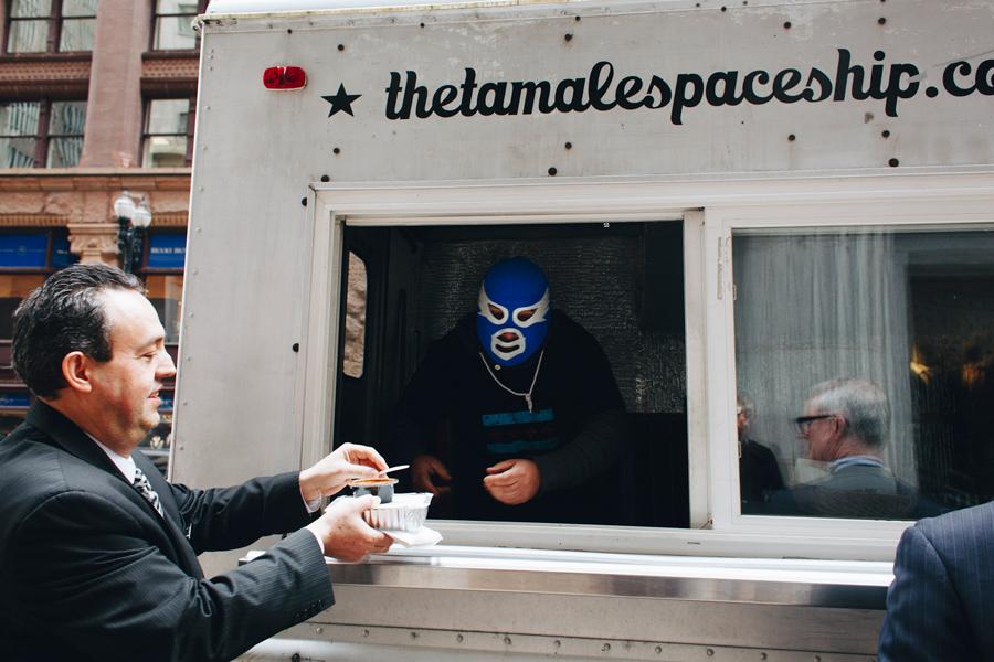 Lucha libre enthusiast Pepe Balanzar serves a customer of his Tamale Spaceship food truck.