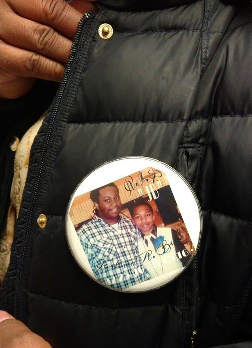 Tiffaney Boxley wears a pin with a photo of her son