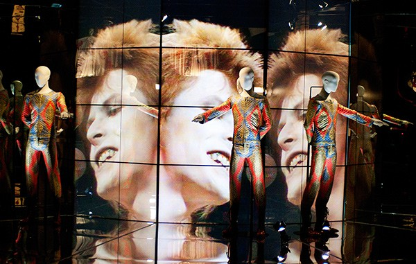 """Bowie's Top of the Pops performance plays on a loop behind his quilted """"Starman"""" suit."""