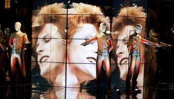 """Bowie's <i>Top of the Pops</i> performance plays on a loop behind his quilted """"Starman"""" suit."""
