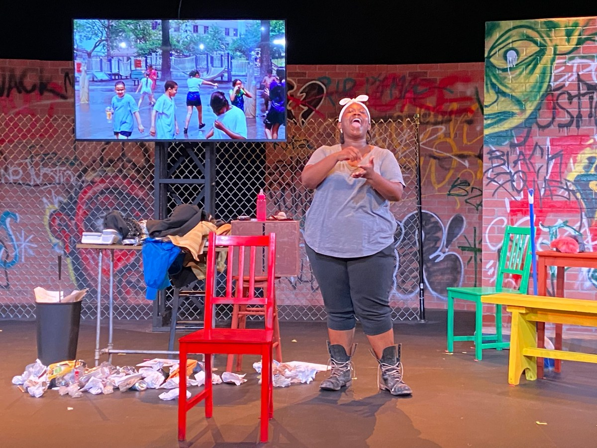 Actor on set with graffiti, chairs, and scattered papers