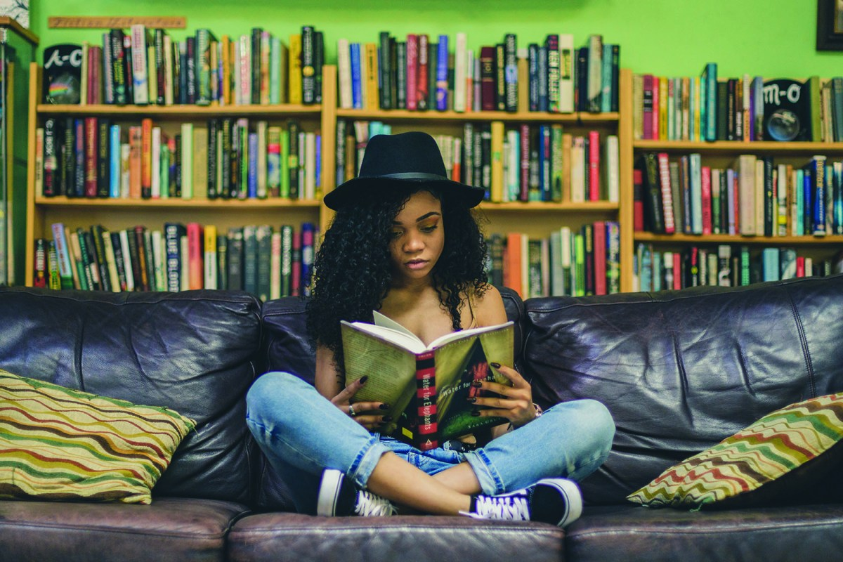 A woman wearing a hat sits cross-legged on a couch while reading a book.