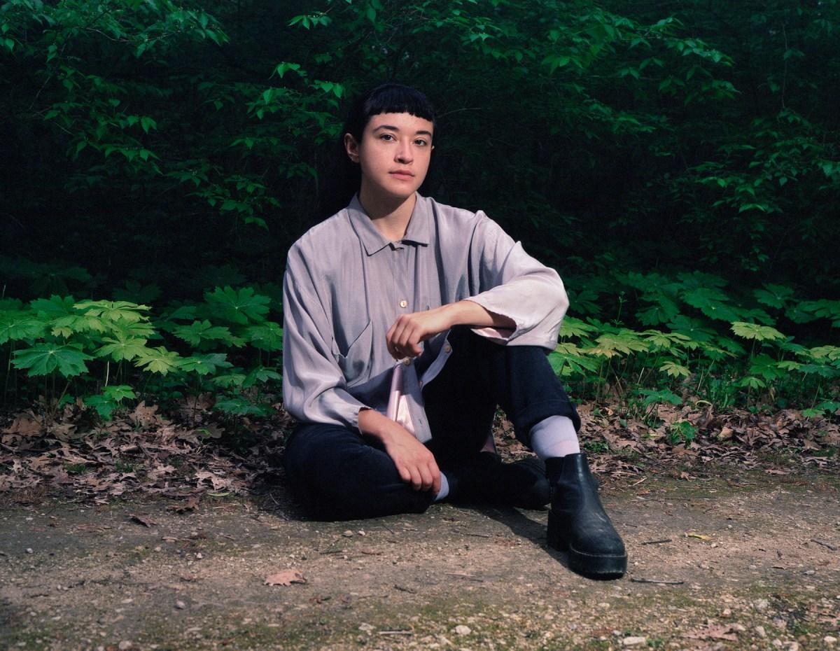 musician Macie Stewart seated on the ground