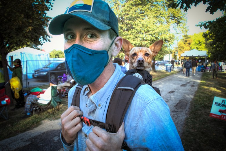 Nick Gondek carries his dog Cashew in a backpack at the Hyde Park Jazz Festival.