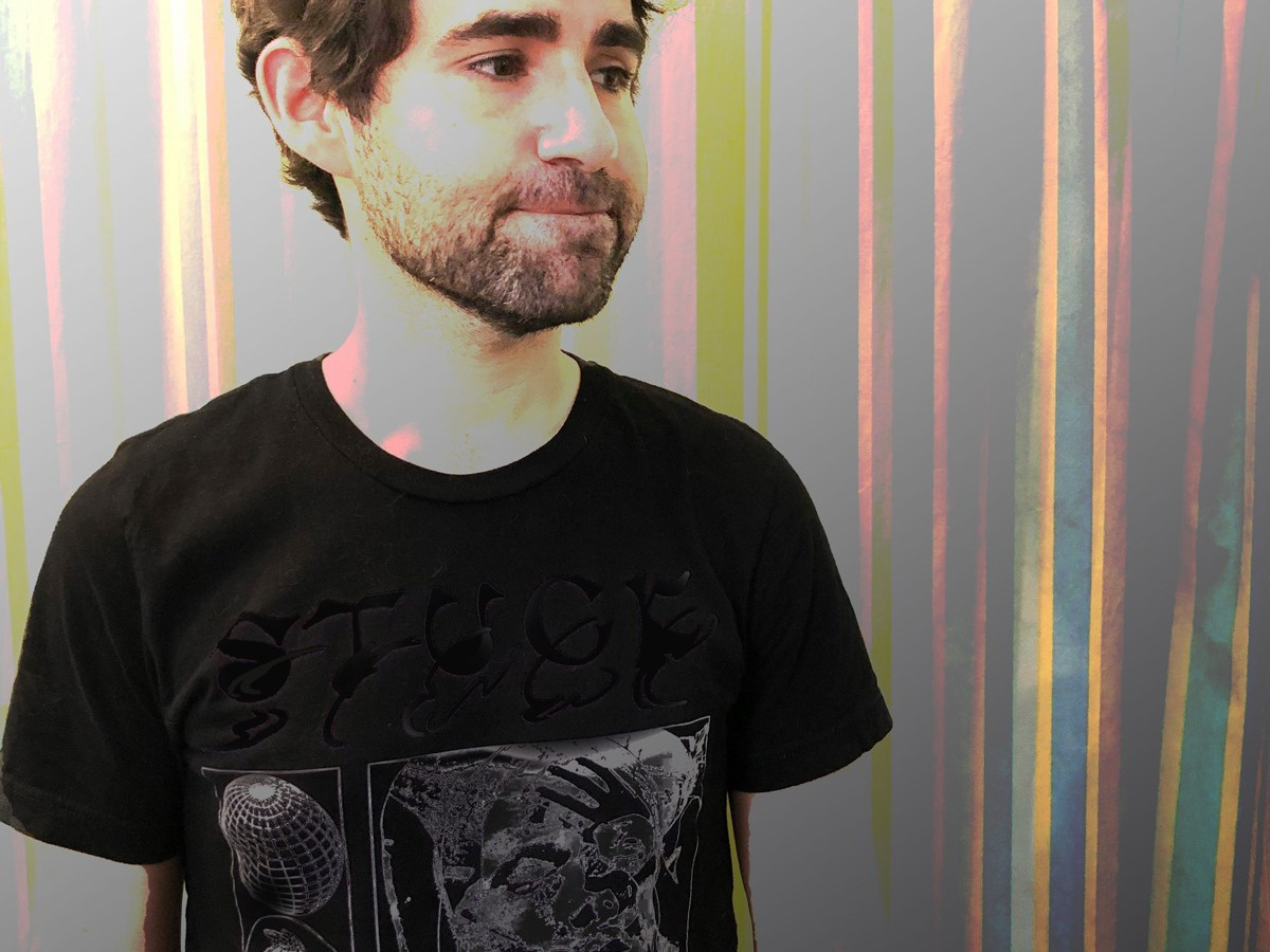 Ben Grigg standing against a murky background