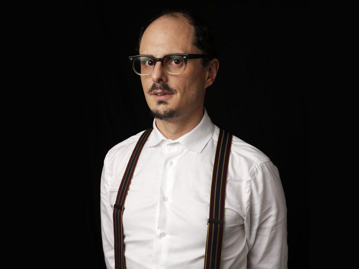Socalled, aka Joshua Dolgin, in a white button-down shirt, suspenders, and glasses